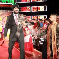 Jinder Mahal walking down the catwalk with his title belt, flanked by the Sign brothers.
