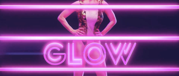 Glow title screen, woman standing behind pink wrestling ring ropes