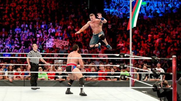 Cena jumps off the top rope towards Rusev