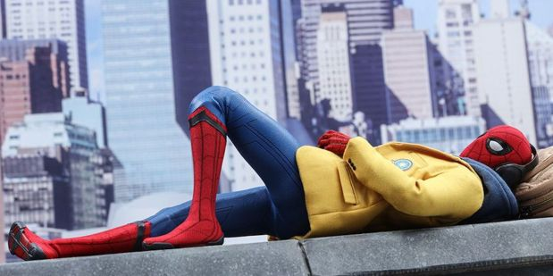 Spiderman lying down on a ledge relaxng with headphones wearing his yellow academic decathlon jacket
