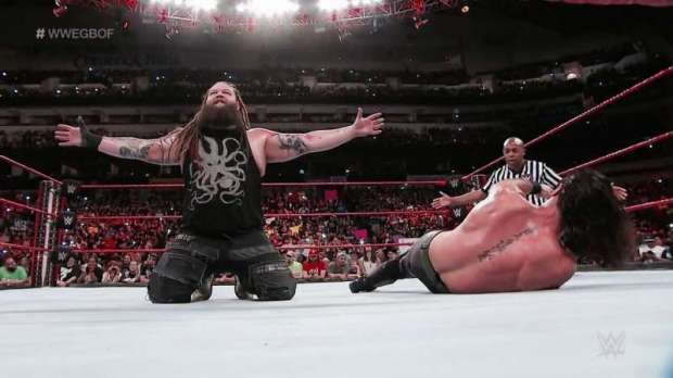 Bray Wyatt celebrates while Rollins lies on the canvas