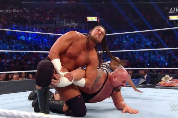 Big Cass has the Big Show in an armlock