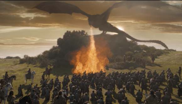 Drogon breathing fire atop a hill