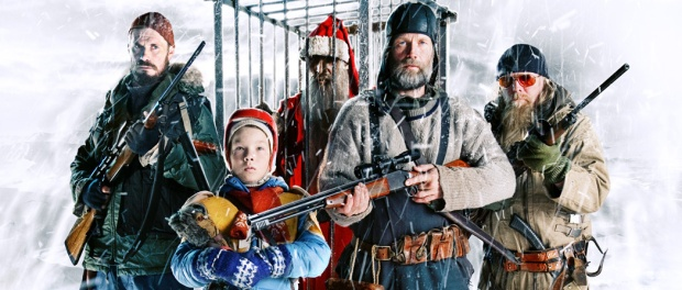 The crew from Rare Exports posing with shotguns in front of a caged Santa