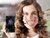 Woman holding a smartphone up behind shattered glass, the effect of the glass contorts her face into a demonic smile