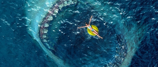 Woman floating on the water with giant shark surfacing towards her