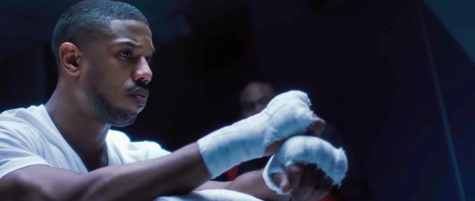 Adonis Creed resting on ropes with hand wraps on and gloves off.